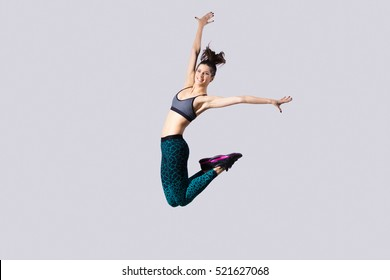 Teenager girl jumping. One happy attractive gorgeous young fit modern woman in aquamarine sportswear with ponytail working out, dancing, jumping with joy, full length, studio image on gray background
