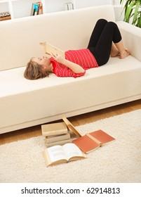 Teenager girl laying on sofa and reading books in living room