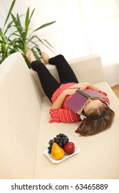 Teenager girl laying on sofa with book covering her face, listening to music
