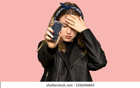 Teenager girl with leather jacket upset with a broken phone on isolated pink background