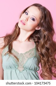 A teenager girl with long curly hair in green dress