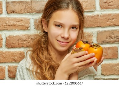 Teenager girl with long hair holding persimmon on background of brick wall.