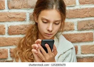 Teenager girl with long hair is typing message on mobile phone on background of brick wall.