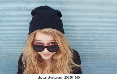 A teenager girl looking up with sunglasses and a beenie