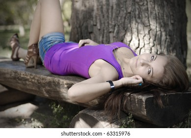 Teenager girl lying on the log bench in autumn park