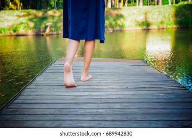 Teenager girl making a step bootlessly on the wooden pier and moving forward to the water, new opportunity concept. selective focus.