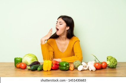 Teenager girl with many vegetables yawning and covering wide open mouth with hand