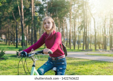 Teenager girl on a bicycle in the park.