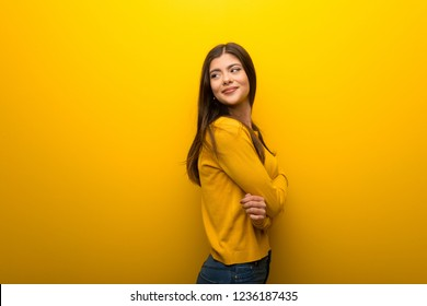 Teenager girl on vibrant yellow background looking over the shoulder with a smile
