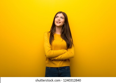 Teenager girl on vibrant yellow background looking up while smiling