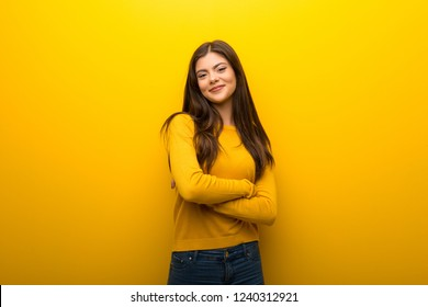 Teenager girl on vibrant yellow background keeping the arms crossed in frontal position