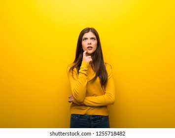 Teenager girl on vibrant yellow background having doubts while looking up