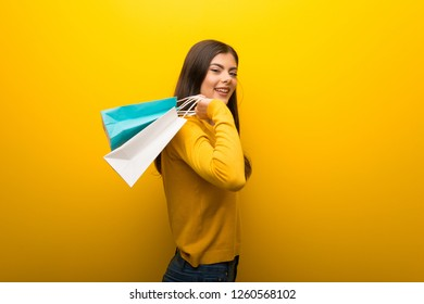 Teenager girl on vibrant yellow background holding a lot of shopping bags