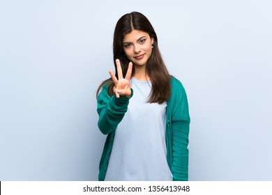 Teenager girl over blue wall happy and counting three with fingers