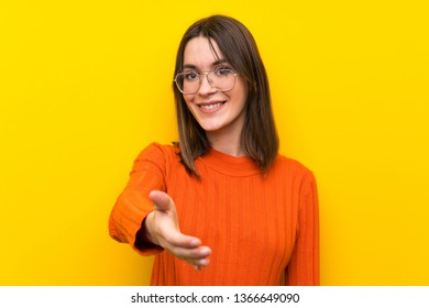Teenager girl over blue wall handshaking after good deal