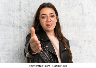 Teenager girl over grunge wall handshaking after good deal