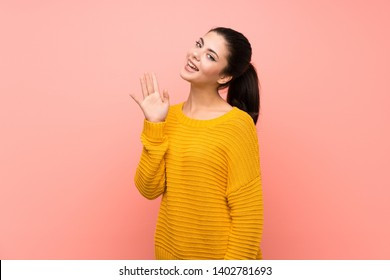 Teenager girl  over isolated pink wall saluting with hand with happy expression