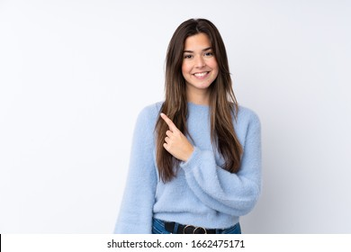Teenager girl over isolated white background pointing to the side to present a product