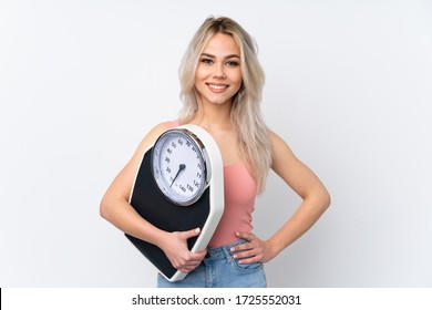 Teenager girl over isolated white background with weighing machine