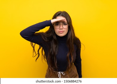 Teenager girl over isolated yellow wall looking far away with hand to look something