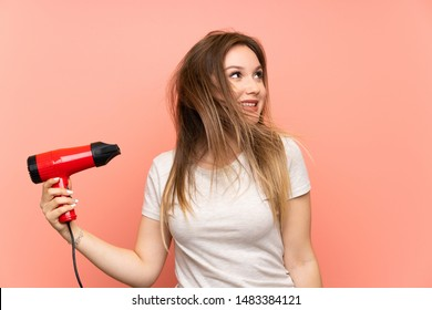 Teenager girl over pink background with hair dryer