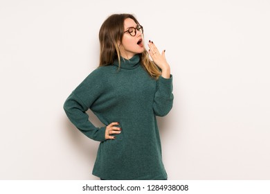 Teenager girl over white wall yawning and covering wide open mouth with hand