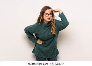 Teenager girl over white wall looking far away with hand to look something