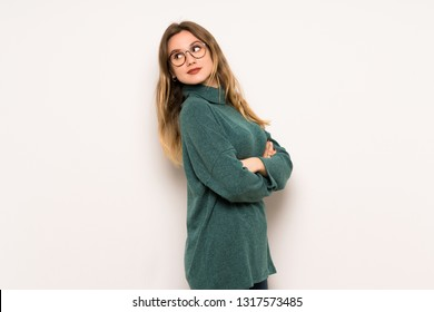 Teenager girl over white wall looking over the shoulder with a smile