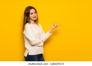 Teenager girl over yellow wall pointing finger to the side in lateral position