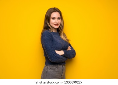 Teenager girl over yellow wall with arms crossed and looking forward