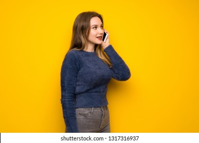 Teenager Girl Over Yellow Wall Keeping A Conversation With The Mobile Phone