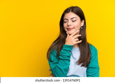 Teenager girl over yellow wall thinking an idea