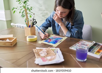 Teenager girl painting with watercolors, sitting at home at the table. Art, education, creativity, teenage hobbies