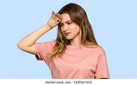 Teenager girl with pink sweater with tired and sick expression on isolated blue background