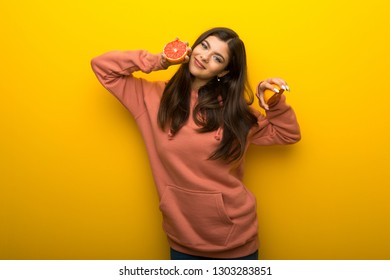 Teenager girl with pink sweatshirt on yellow background with oranges