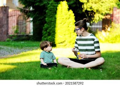 Adolescent, jouant avec sa petite soeur avec des bulles de savon au coucher du soleil