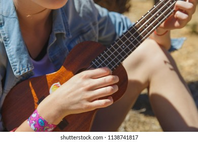 Teenager girl playing ukulele - hawaiian guitar