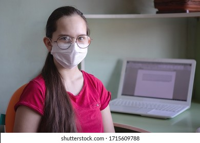 Teenager girl in a protective medical mask and glasses. Online home schooling. Social distance, coronavirus epidemic. Selected Focus.