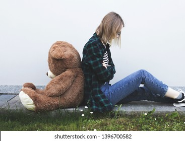 Teenager Girl puberty problems concept, sitting on the ground with toy plush bear. Angry girl.