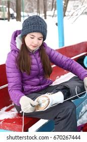 teenager girl put on skates before ice skating close up photo