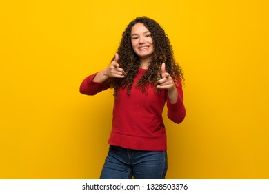 Teenager girl with red sweater over yellow wall pointing to the front and smiling