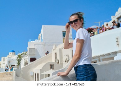 Teenager girl resting on Greek island Santorini, female looking at camera, background white architecture of village Oia, sea, sky in clouds, copy space