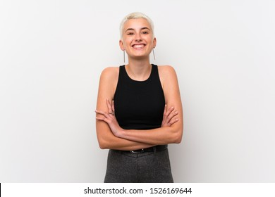 Teenager girl with short hair over white wall keeping the arms crossed in frontal position