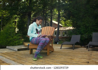 Teenager girl sit on a Muskoka chair reading on a tablet. The girl is wearing colourful clothes. A cottage nestled between trees is visible in the background.