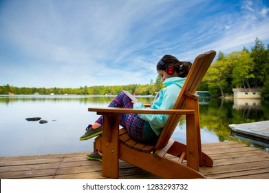 Teenager girl sit on a Muskoka chair reading a tablet and enjoying music on eartphones. The girl is wearing colourful clothes. Lake cottages nestled between trees are visible in the background.