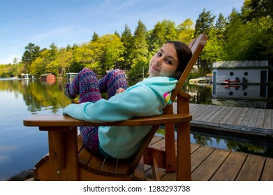 Teenager girl sit on a Muskoka chair enjoying the calming landscape. The girl is wearing colourful clothes and is smiling. Lake cottages nestled between trees are visible in the background.