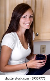 Teenager Girl Sitting on the Counter Drinking Coffee