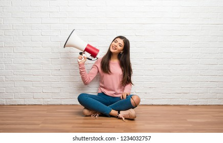 Teenager girl sitting on the floor in a room holding a megaphone