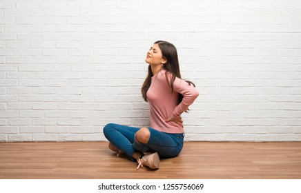 Teenager girl sitting on the floor in a room suffering from backache for having made an effort