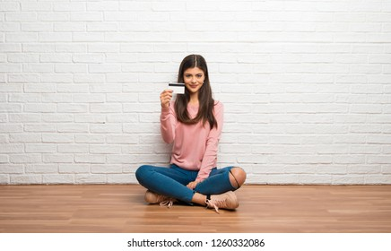 Teenager girl sitting on the floor in a room holding a credit card